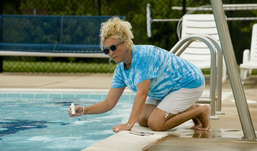 Darla Sue Moomaw, manager of the Woodstock Pool, takes a water sample along the edge of the pool on Tuesday. Moowaw and staff members take water samples for chlorine and pH on a daily basis. Town officials closed the pool Monday after fecal contamination was discovered in the water.   Rich Cooley/Daily
